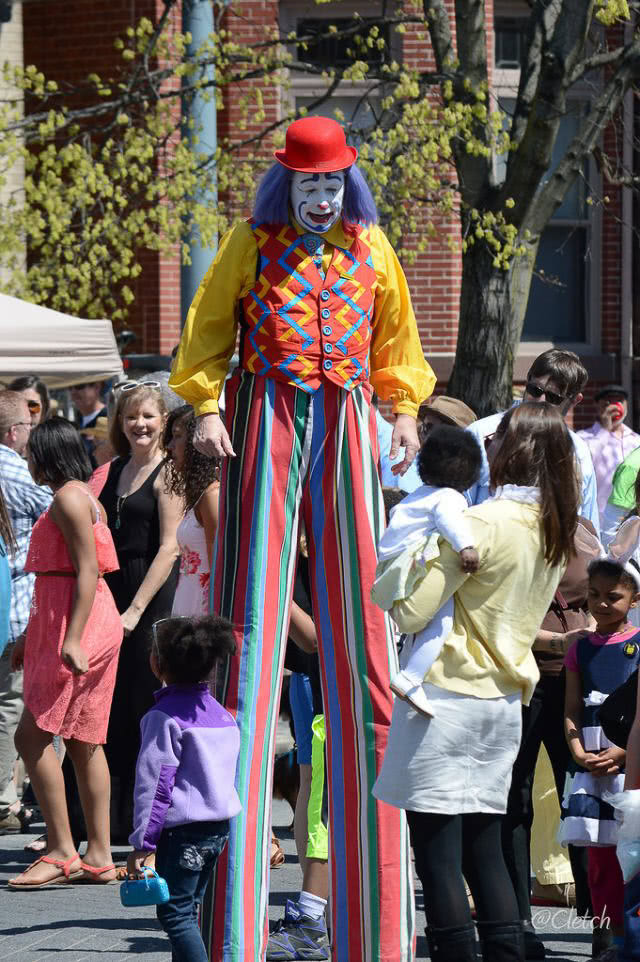A picture of a scary looking clown on stilits